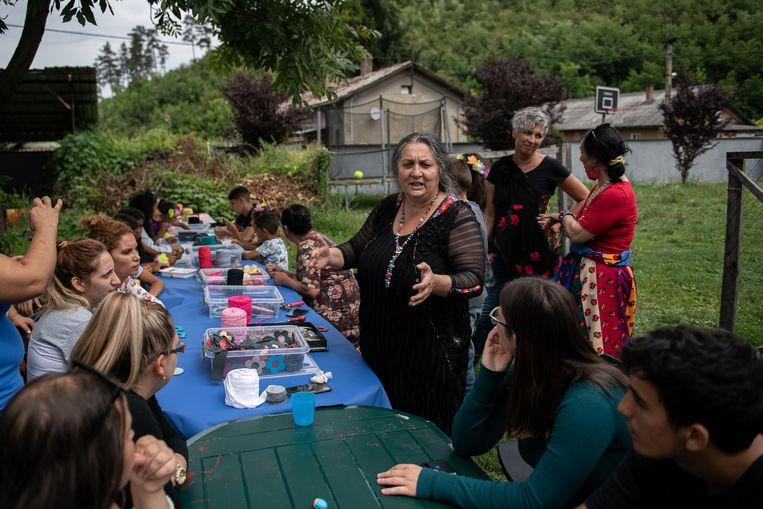 Kinderen uit de nederzettingen in Ózd maken sieraden in de tuin van het opvangcentrum.  Beeld Photo: Dénes Erdős