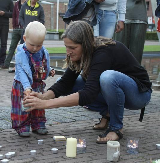 Dit jongetje steekt samen met zijn mama een kaarsje aan voor de overleden Julie en de zwaargewonde Ellen.