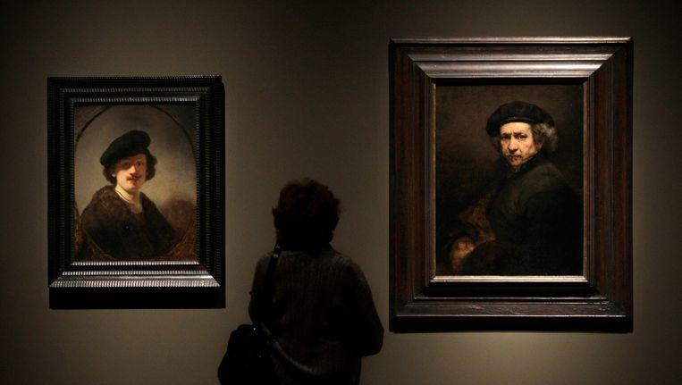 Een bezoeker kijkt naar twee zelfportretten van Rembrandt Beeld AP