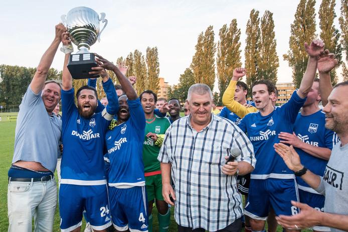 Toernooileider Ben van der Horst (midden) heeft de Arnhem Cup uitgereikt aan aanvoerder Tanju Sahin van Duno. Purrel Fränkel en sponsor Arjen Ploeg helpen hem de trofee omhoog te torsen. Duno versloeg VDZ in de finale met 2-0.