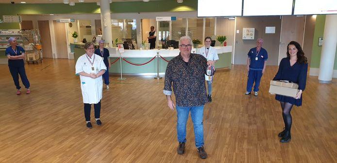 Rob Theunissen (midden) en zijn dochter Layla (rechts) overhandigen de lintjes bij ziekenhuis Bernhoven.
