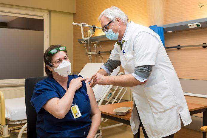 Het Jessa Ziekenhuis begon vanavond al met vaccineren. Op deze foto zet algemeen directeur dokter Yves Breysem het allereerste vaccin bij urgentie-arts en medisch diensthoofd van de spoedafdeling Agnes Meersman.