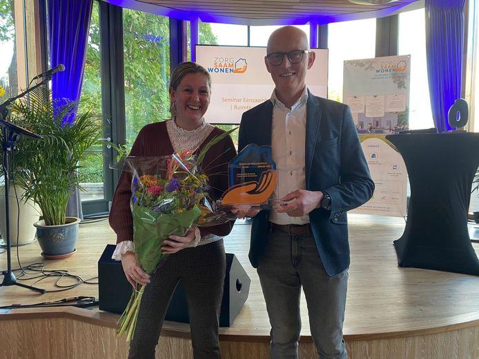 Esther de Voogd(l) en Joost Smit(r) tonen namens Hart van Vathorst de gewonnen Award en de welverdiende bloemen.