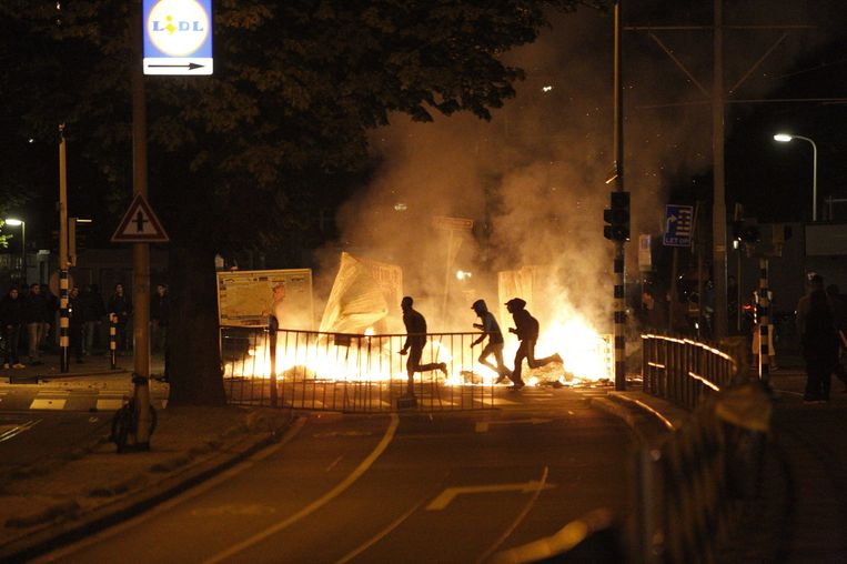 Relschoppers rennen langs een barricade in de Schilderswijk. Beeld epa