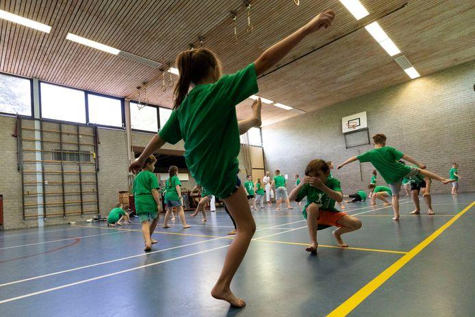 Kinderen krijgen capoeirales op basisschool de Zevensprong.