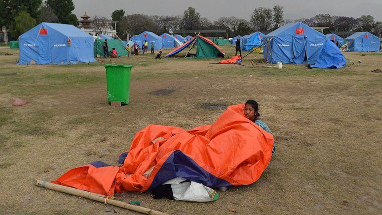 Een inwoonster van Nepal zit in Kathmandu onder een gebroken tent na zware windstoten in een opvangkamp voor overlevenden van de aardbeving. Beeld AFP