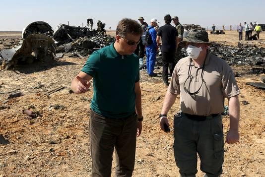 De Russische minister van transport Maxim Sokolov (links) praat met een onderzoeker op de plek waar het vliegtuig neerstortte.