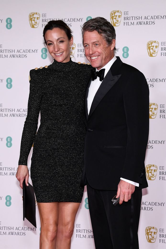 Actor Hugh Grant poses with Anna Eberstein on the red carpet ahead of the BAFTAs in London.