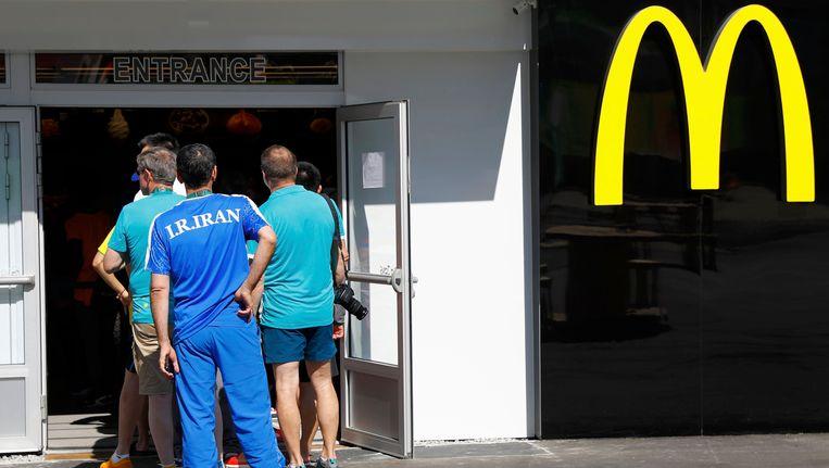 Een Iraniër schuift achteraan de lange wachtrij van de McDonald's in. Beeld REUTERS