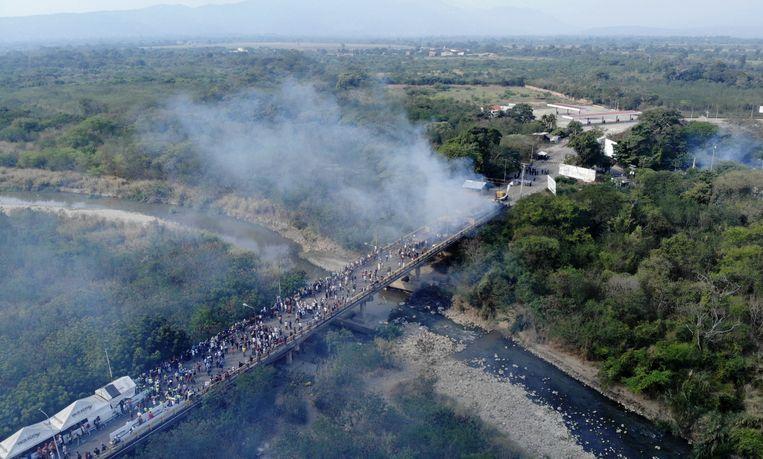 Luchtfoto van de vrachtwagen met humanitaire hulp die door het Venezolaanse leger in brand is gestoken. Beeld AFP