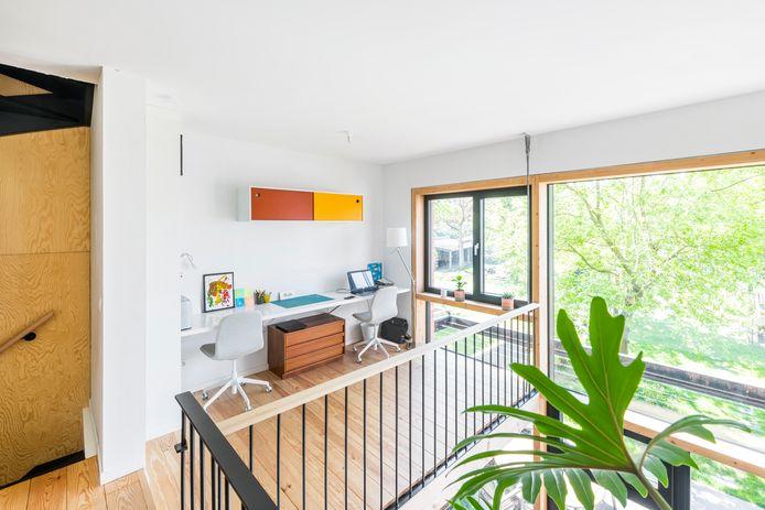 De mezzanine op de eerste verdieping loopt door tot aan het raam. Katrien en Thomas richtten er hun een thuiskantoor in. Net als in de slaapkamers ligt hier een grenen plankenvloer.