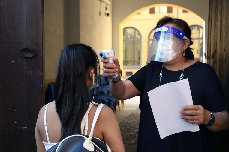 De temperatuur van een leerling wordt gecontroleerd in een school in Modena.  Beeld Photo News