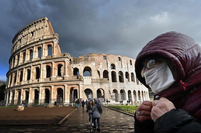 Een toerist met een mondmasker aan het Colosseum in Rome. Beeld AFP