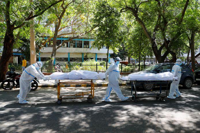 Ziekenhuismedewerkers in New Delhi brengen overleden coronapatiënten weg.
