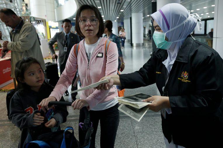Een gezondheidsmedewerker deelt folders uit op de luchthaven van Kuala Lumpur.