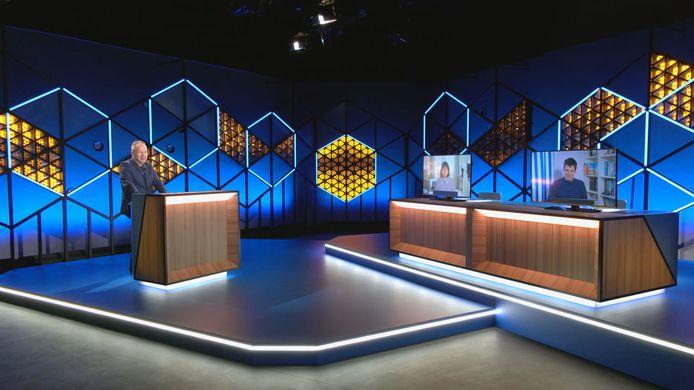 Ben Crabbé presenteert 'Blokken' in een lege studio, waar de kandidaten op schermen te zien zijn.