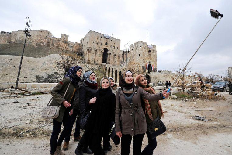 Syriërs met een selfiestick voor de oude citadel in Aleppo.  Beeld Reuters