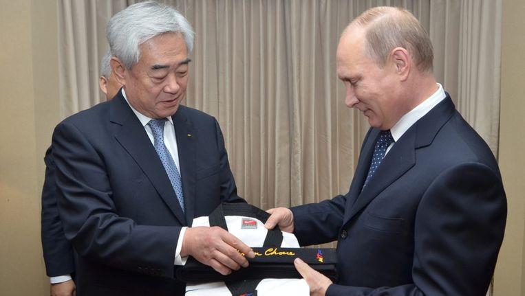Poetin ontvangt de zwarte band van de voorzitter van de Wereld Taekwondo Federatie. Beeld epa