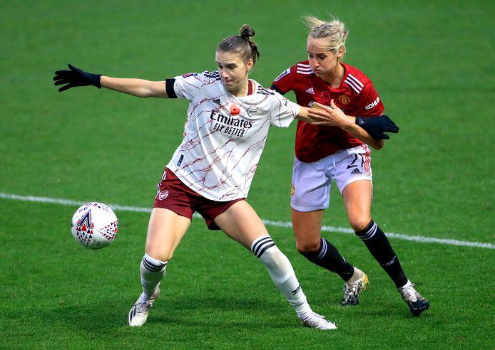 Vivianne Miedema (l) in duel met Manchester United-speelster Millie Turner.