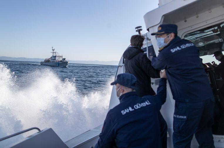 Leden van de Turkse kustwacht waarschuwen een schip van de Griekse kustwacht. Beeld EPA
