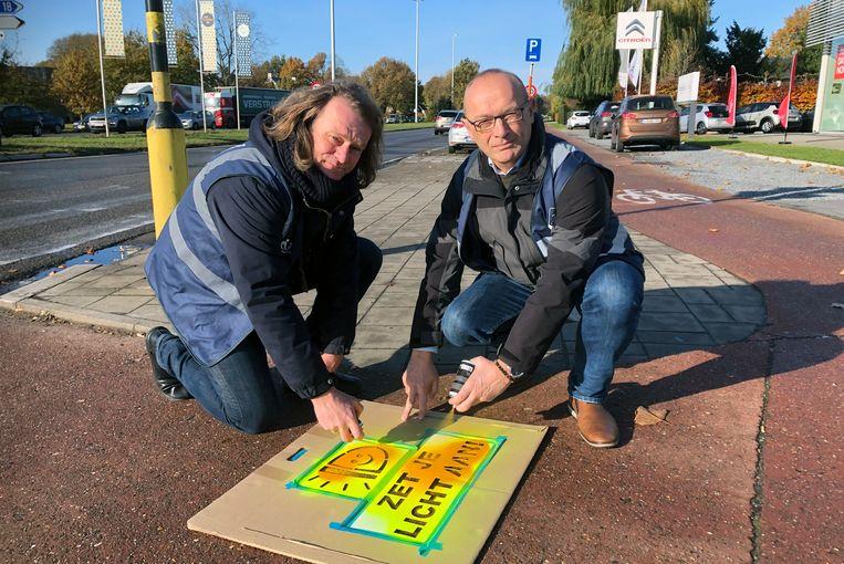 Jan Van Otten en Marc Boogers spuiter de boodschap 'Zet je licht aan'. Ze dragen de blauwe hesjes die de stad uitdeelde aan scholieren