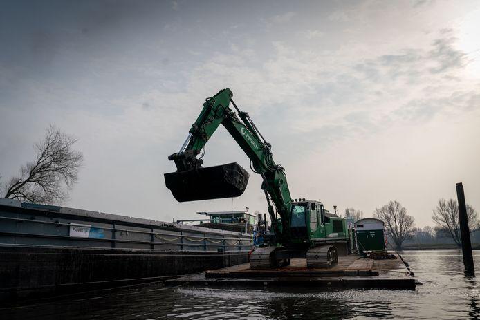 Met een graafmachine wordt de komende zes weken zo'n zesduizend kuub slib uit de Arnhemse defensiehaven gebaggerd.
