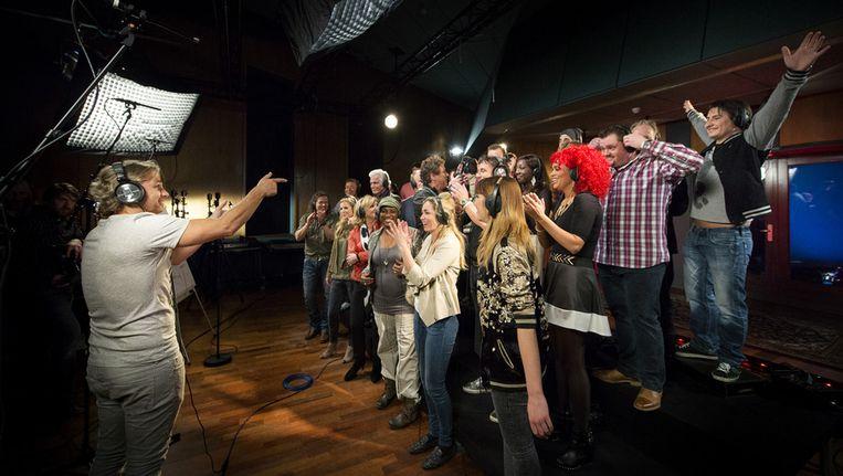 Een groep BN'ers met op de voorgrond John Ewbank tijdens het opnemen van het Koningslied. Het lied zal op 30 april in Ahoy worden gezongen door een groot aantal nationale sterren. Beeld anp
