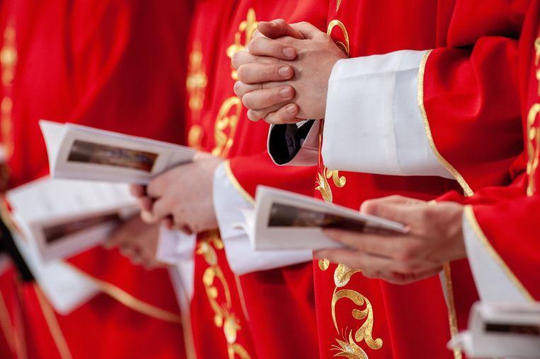 Een rooms-katholieke geestelijke bidt in de Sint-Pietersbasiliek in het Vaticaan. Beeld Photo News