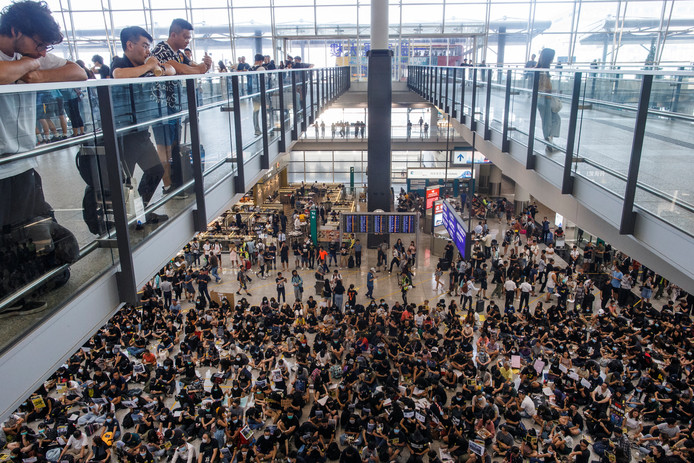 Honderden demonstranten bevolken de aankomsthal van Hongkong International Airport in Hongkong.