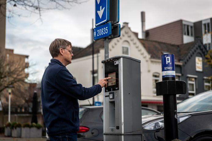 Een man betaalt om te parkeren bij een parkeerautomaat op de Markt in Helmond.