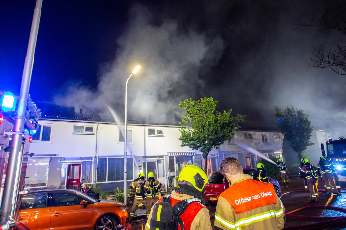 De brandweer probeert de vlamvattende daken in de Frederik Hendrikstraat te blussen.