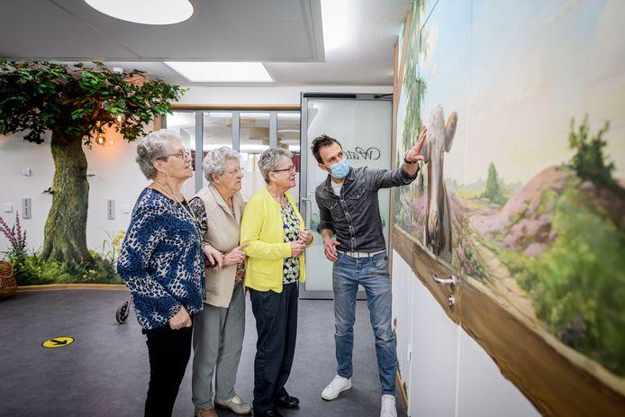 Kunstenaar Chris Veldhof toont zijn muurschildering in de Bloemenhof aan van linksaf Marietje Koopmans, Sien Koopman en Sinie Boerman.