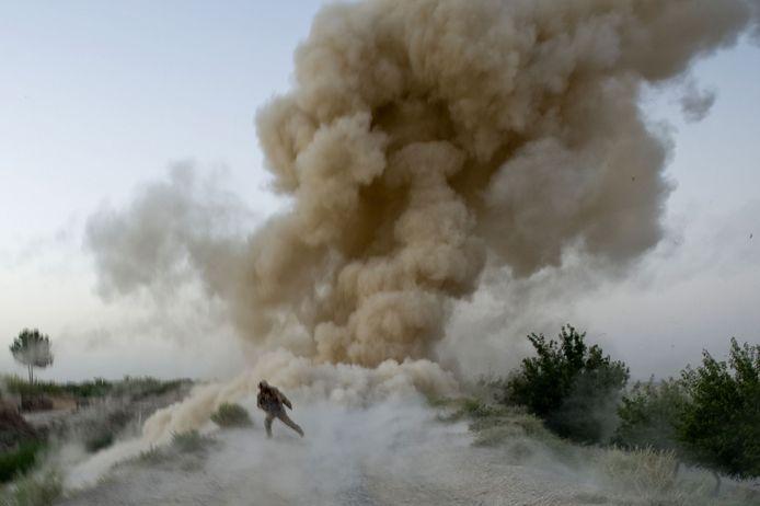 Een Amerikaanse soldaat zoekt dekking wanneer een bermbom van de Taliban ontploft in Afghanistan