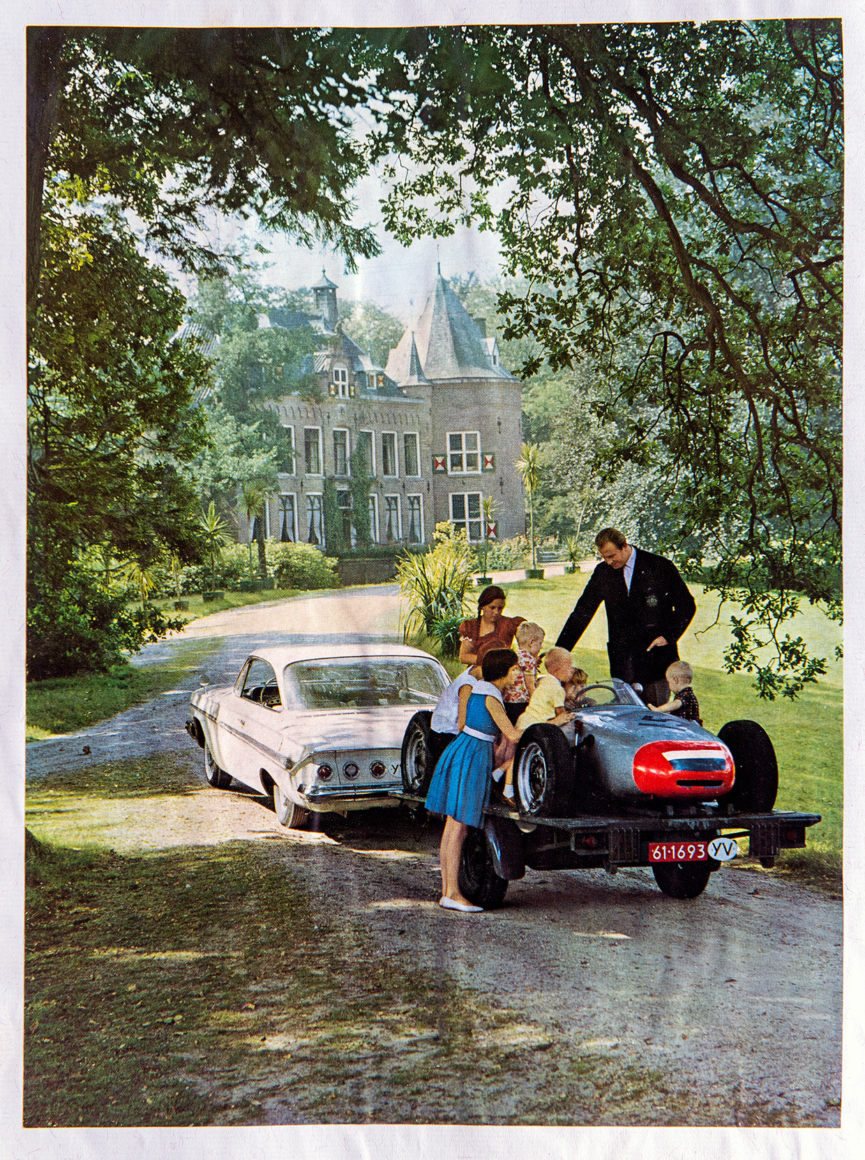 Carel Godin de Beaufort, netjes gekleed voor de Elegance, showt trots een raceauto aan een groep kinderen. Op de achtergrond het kasteel. Beeld Klaas Jan van der Weij