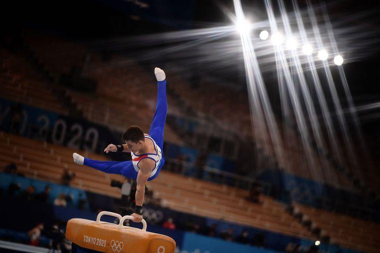 Nikita Nagornyy, die Rusland het goud schonk in de teamfinale allround, schommelt op het paard in een bijna leeg Ariake Gymnastics Centre in Tokio. Beeld AFP