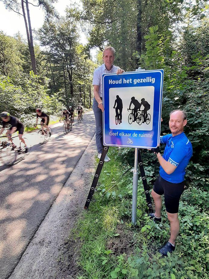 Wethouder Frank van Raak (Alphen-Chaam, op de ladder) en zijn Bredase collega Daan Quaars bij een van de nieuwe fietsborden langs de fietsallee tussen Ulvenhout en Alphen.