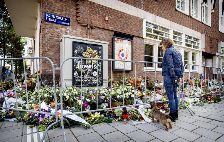 Een passant kijkt bij de bloemenzee bij het kantoor van de doodgeschoten advocaat Derk Wiersum.  Beeld ANP
