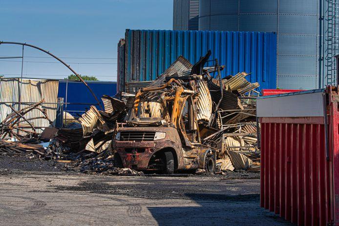 Restanten van de loodsbrand bij overslagbedrijf Edink. Eén van de afgebrande heftrucks is nog zichtbaar.