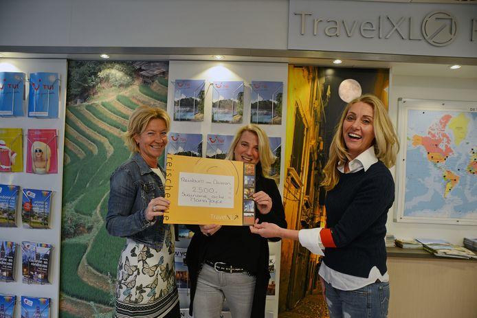 Martine Wakkee van Travel XL Van Oeveren (links) overhandigt de cheque aan Marga Wasser (midden) en Joyce van den Biggelaar van de JA Foundation.