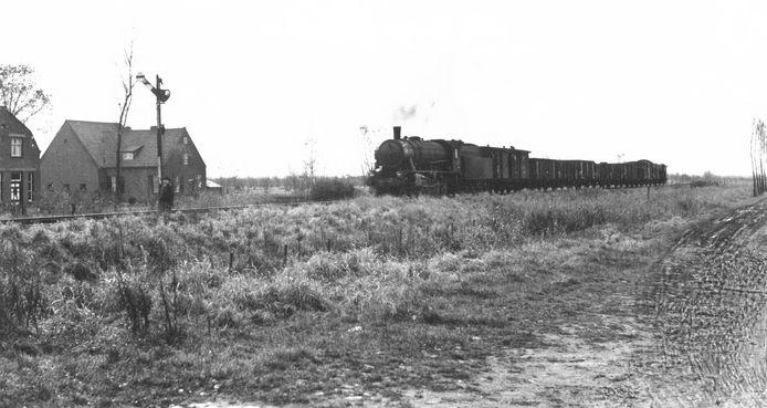 Op de Langstraatspoorlijn nadert een goederentrein, getrokken door een stoomlocomotief de spoorwegovergang aan de Besoyensestraat. De foto is rond 1950 gemaakt.