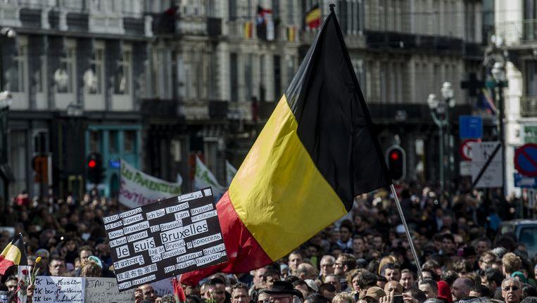 De Belgische vlag wordt hooggehouden tijdens de Mars tegen Terreur. Beeld anp