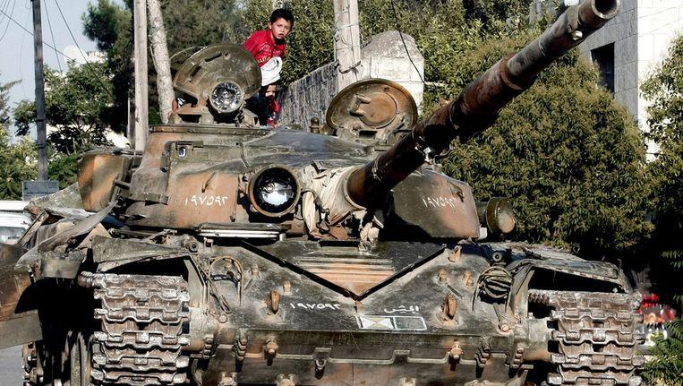 Een Syrisch jongetje op een kapotte tank in Azaz, zo'n twintig kilometer van Aleppo Beeld ap