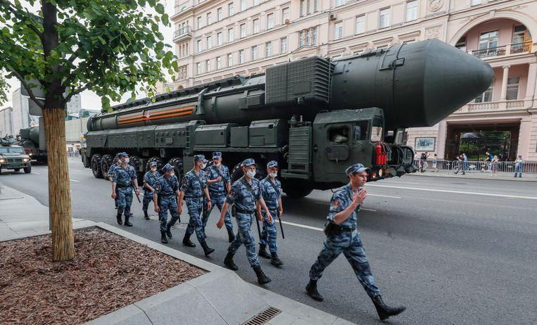 Russische politie loopt langs een RS-24 Yars op weg naar de militaire parade op het Rode Plein in Moskou.  Beeld EPA