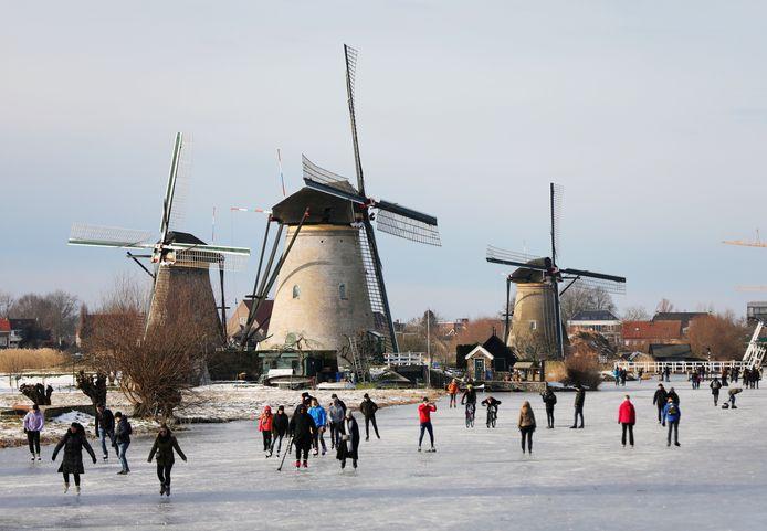 Midden op de foto filmt een schaatser met rode jas de schaatsdrukte bij de molens van Kinderdijk, zondag 14 februari. Hij was bepaald niet de enige.