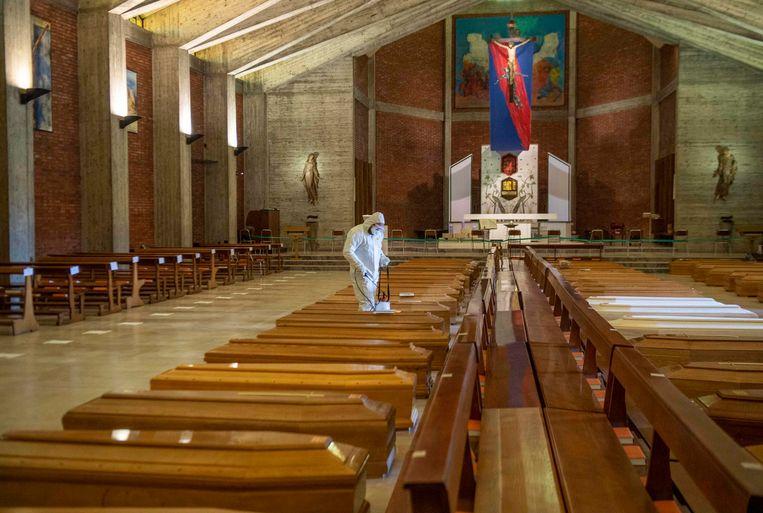 Italiaanse militairen ontfermen zich over 45 lijkkisten van coronaslachtoffers in een kerk in Bergamo, eind maart.  Beeld EPA