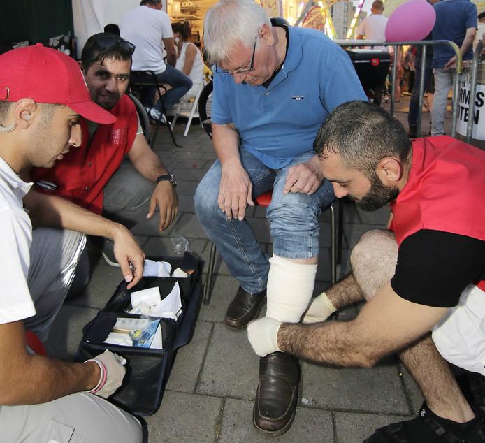 Drie Syrische vluchtelingen helpen als vrijwilliger op de kermis in Oss.