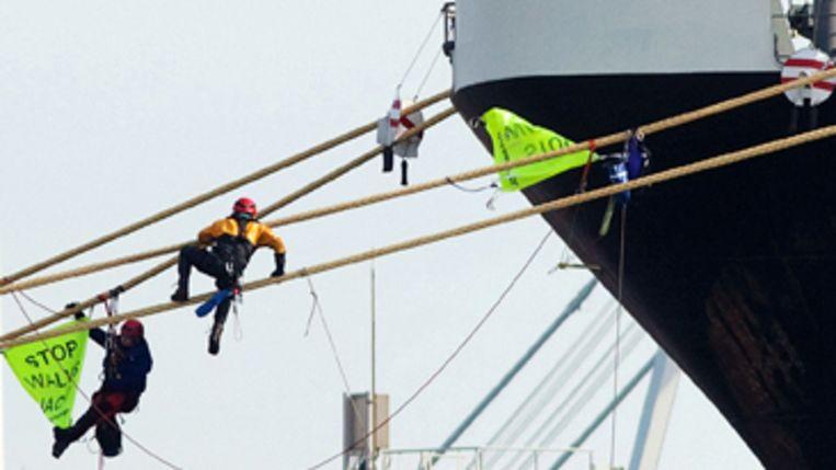 Actievoerders van Greenpeace proberen te voorkomen dat het schip uitvaart. (Greenpeace) Beeld