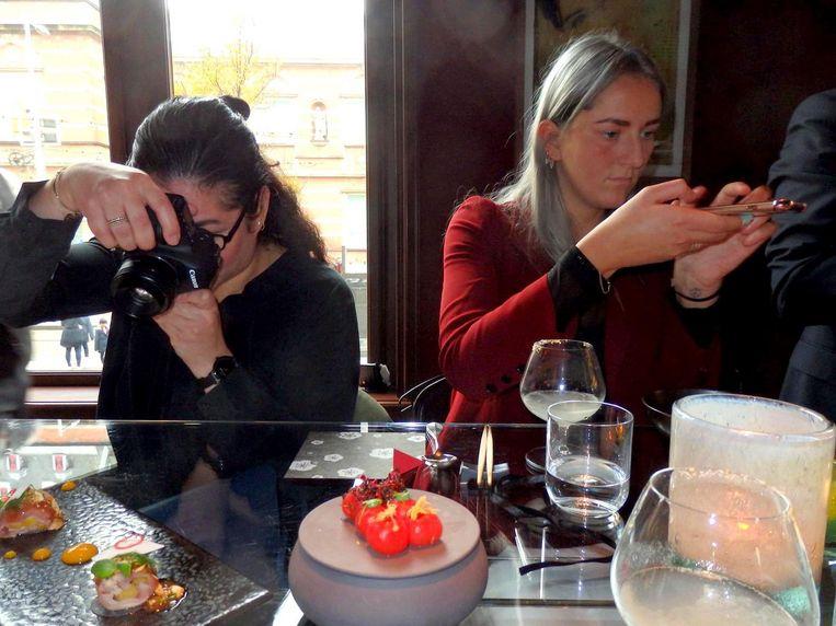 Vaak gezien tijdens schuimfeestjes: altijd eerst foto's, zoals anderen bidden voor het eten. Beeld Schuim