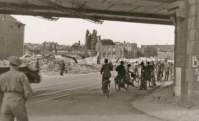 Na de bevrijding van Arnhem. Teruggekeerde evacués worden door fotograaf P.J. de Booys vastgelegd terwijl ze vanonder de Velperpoort de verwoesting bekijken die de Slag om Arnhem en het bombardement in april 1945 veroorzaakt hebben in onder meer de Steenstraat.