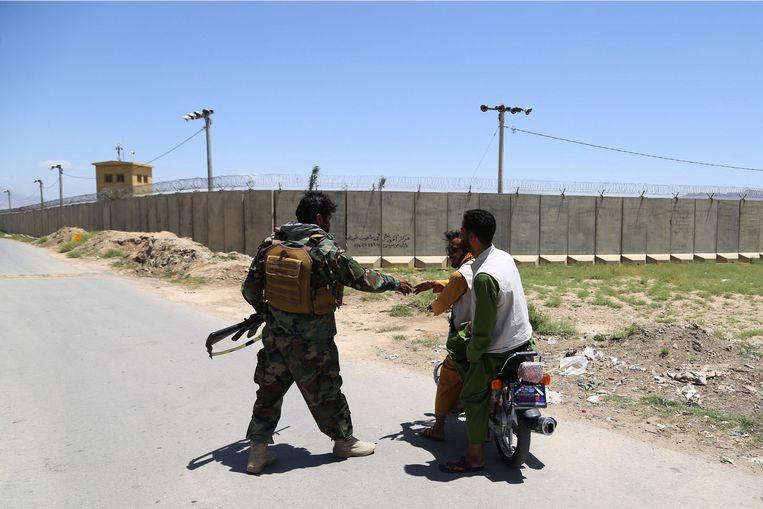 Een soldaat begroet twee voorbijgangers bij de luchtmachtbasis in Bagram. Beeld AFP